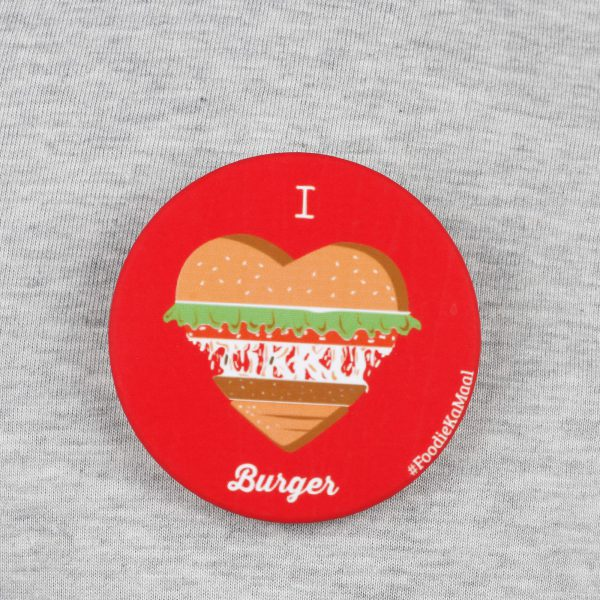 front view of red colour badge or fridge magnet with i love burger printed on it